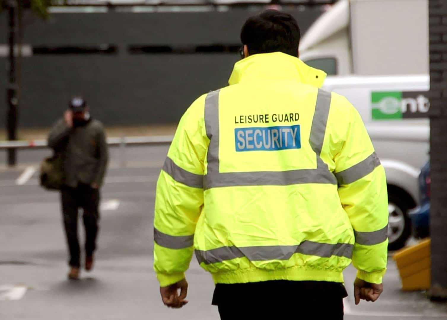 LGS guard in hivis walking towards person