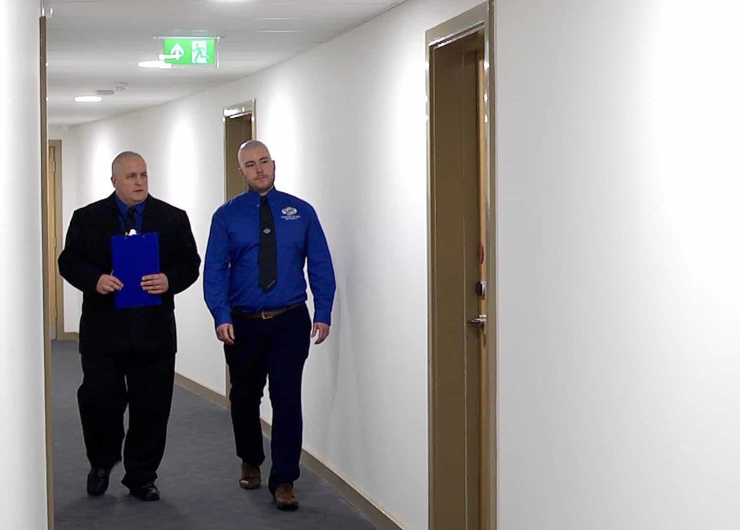 LGS guards walking hotel corridor